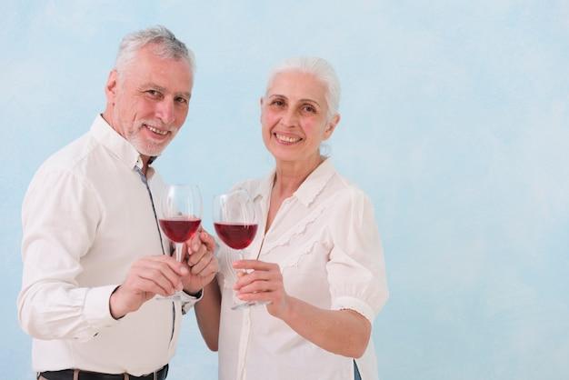 Ritratto del marito e della moglie felici che tengono il vetro di vino che esamina macchina fotografica