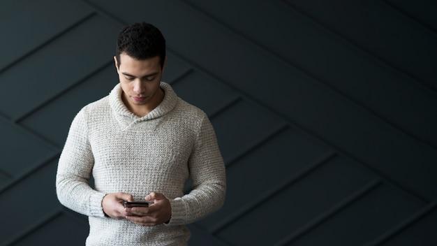 Ritratto del maschio adulto che manda un sms sul suo telefono cellulare