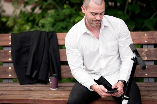 Ritratto del maschio adulto che passa in rassegna telefono cellulare