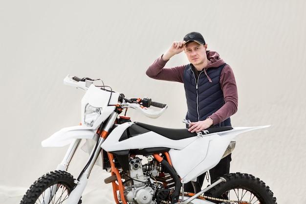 Ritratto del maschio adulto che prova a riparare motociclo