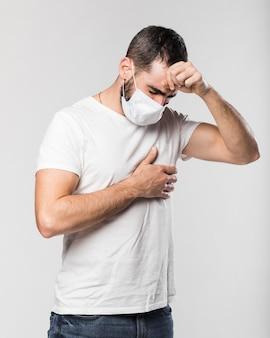 Ritratto del maschio adulto con la tosse della maschera di protezione