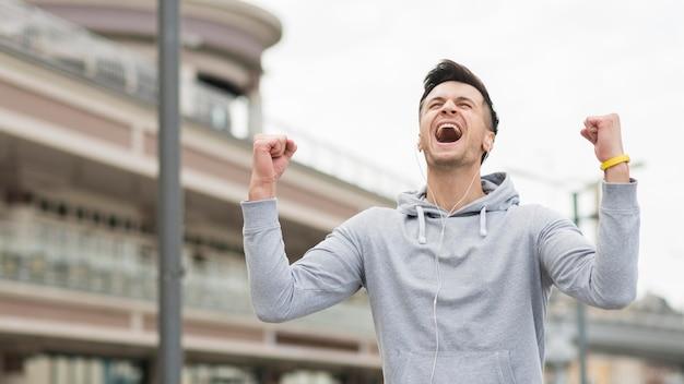 Ritratto del maschio felice che celebra dopo l'allenamento
