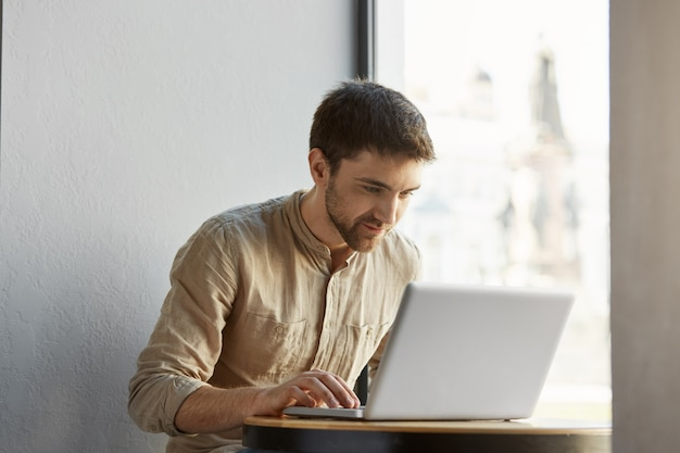 Ritratto del maschio indipendente caucasico attraente in abbigliamento casual che lavora duro sul suo computer portatile in caffè con l'espressione felice. concetto di affari.