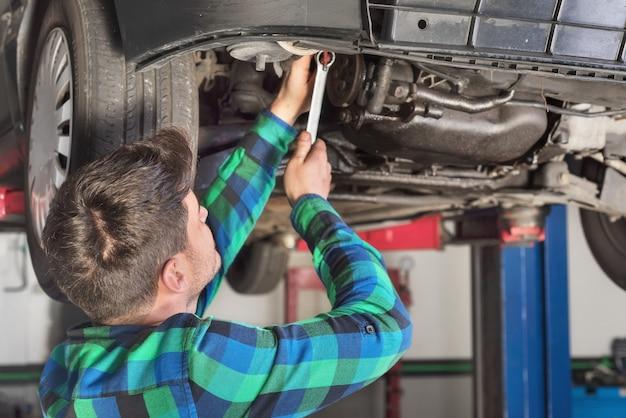 Ritratto del meccanico che ripara con una chiave un'auto alzata.