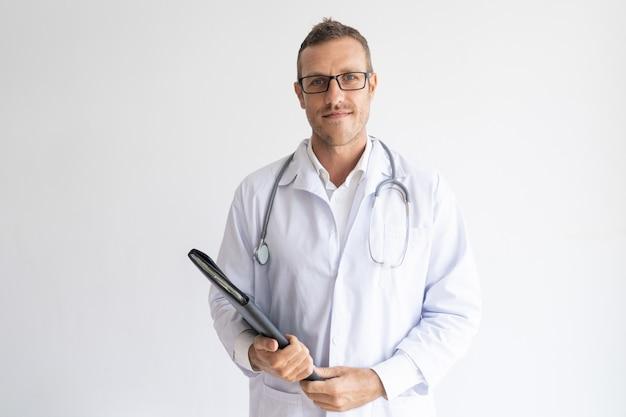 Ritratto del medico sicuro che indossa i vetri che tengono cartella.