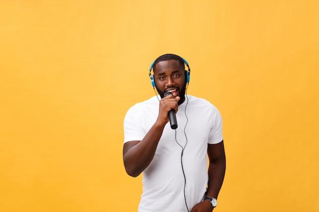 Ritratto del microfono africano bello elegante positivo allegro della tenuta dell'uomo