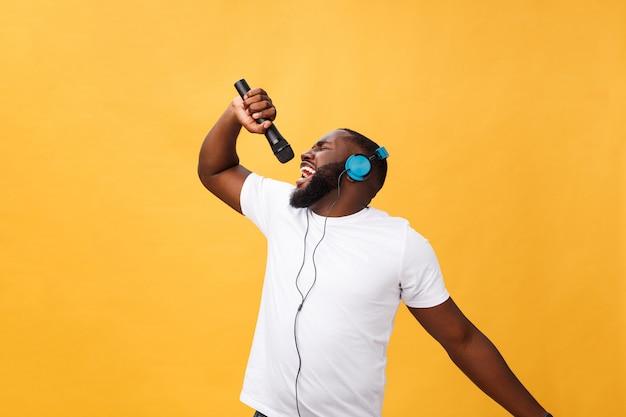Ritratto del microfono africano bello elegante positivo positivo allegro della tenuta dell'uomo e di avere cuffie