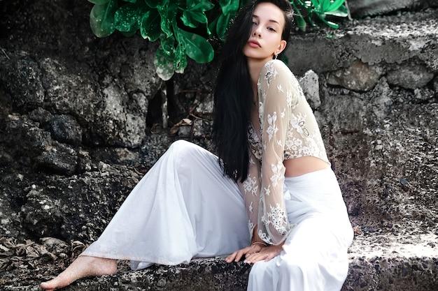 Ritratto del modello bella donna caucasica con i capelli lunghi scuri in pantaloni classici a gamba larga in posa vicino a rocce e sfondo verde esotico tropicale foglie