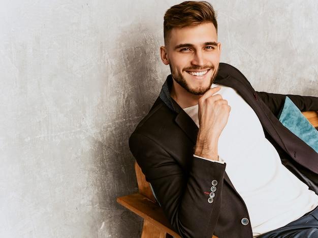 Ritratto del modello bello dell'uomo d'affari dei pantaloni a vita bassa che indossa vestito nero casuale.