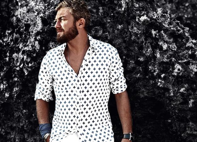Ritratto del modello bello dell'uomo di modo che indossa i vestiti bianchi che posano vicino alle rocce sulla spiaggia