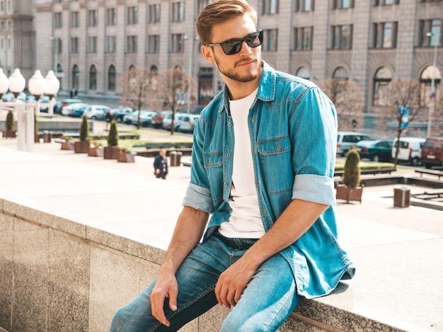 Ritratto del modello dell'uomo d'affari lumbersexual alla moda bello dei pantaloni a vita bassa. uomo vestito con abiti giacca di jeans.