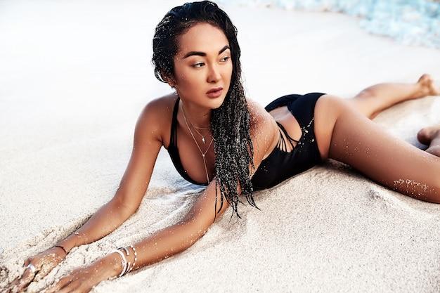 Ritratto del modello di bella donna caucasica preso il sole con i capelli lunghi scuri in costume da bagno nero sdraiato sulla spiaggia estiva con sabbia bianca
