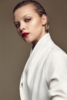 Ritratto del modello di donna bruna elegante bella moda con trucco sera e labbra rosse in giacca bianca
