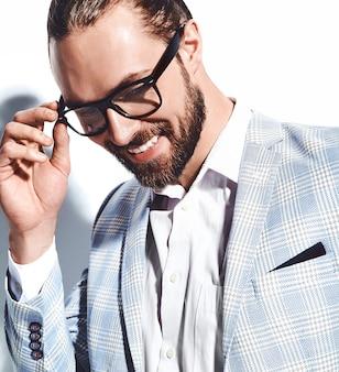 Ritratto del modello di uomo d'affari alla moda hipster alla moda bello vestito in elegante abito azzurro in bicchieri su bianco