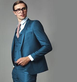 Ritratto del modello di uomo d'affari alla moda hipster alla moda bello vestito in elegante abito blu in posa su sfondo grigio in studio con gli occhiali
