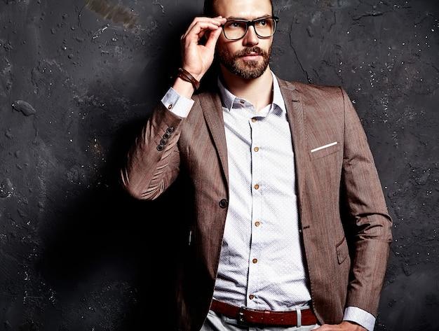 Ritratto del modello di uomo d'affari alla moda hipster alla moda bello vestito in elegante abito marrone con gli occhiali vicino al muro scuro