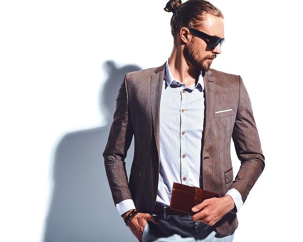 Ritratto del modello di uomo d'affari alla moda hipster alla moda bello vestito in elegante abito marrone in occhiali da sole