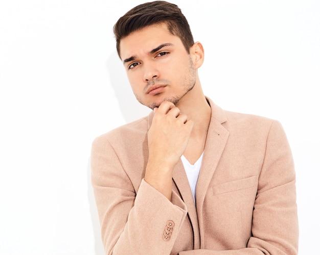 Ritratto del modello di uomo d'affari alla moda moda bella vestita in elegante abito rosa chiaro in posa. metrosexual