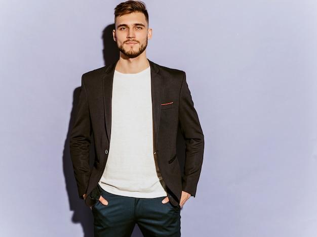 Ritratto del modello di uomo d'affari serio bello hipster che indossa abito nero casual.