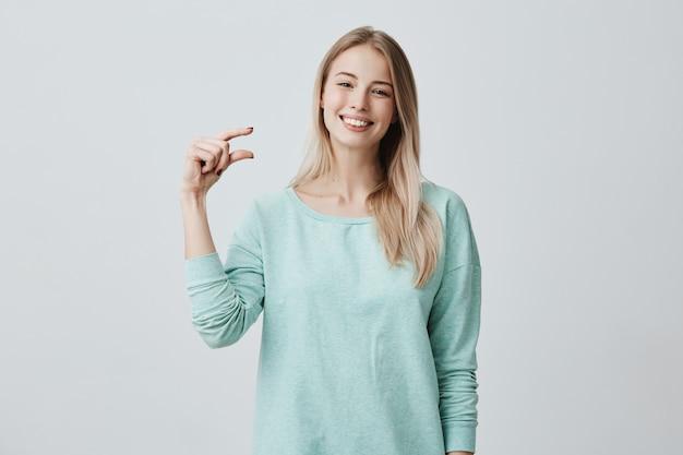 Ritratto del modello femminile caucasico felice soddisfatto con la bionda che sorride ampiamente dimostrando la dimensione di qualcosa