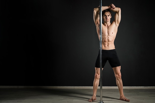 Ritratto del modello maschio che posa come ballerino del palo