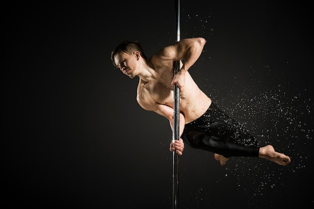 Ritratto del modello maschio professionale che esegue una danza del palo