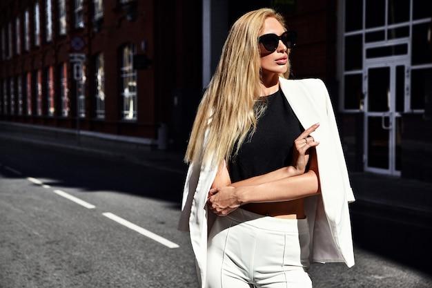Ritratto del modello moderno della donna di affari di modo sexy in vestito bianco che posa sui precedenti della via