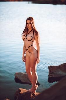 Ritratto del modello sensuale del bikini che sta sulla spiaggia. bella giovane donna che posa in costume da bagno sulla riva del mare