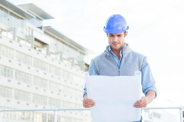 Ritratto del modello sicuro della lettura dell'architetto fuori della costruzione