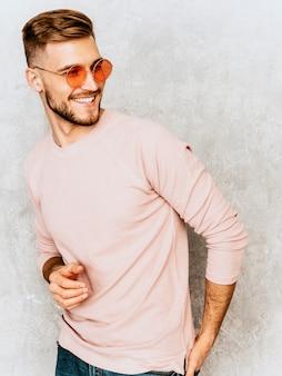 Ritratto del modello sorridente bello del giovane che indossa i vestiti casuali di rosa di estate. uomo alla moda di modo che posa in occhiali da sole rotondi