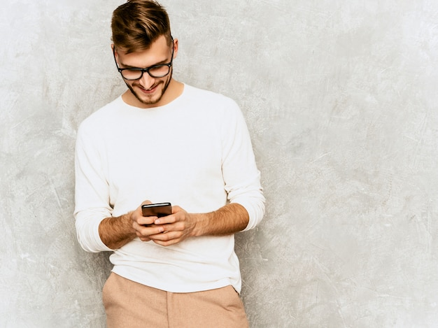 Ritratto del modello sorridente bello dell'uomo d'affari dei pantaloni a vita bassa che indossa i vestiti bianchi casuali di estate.