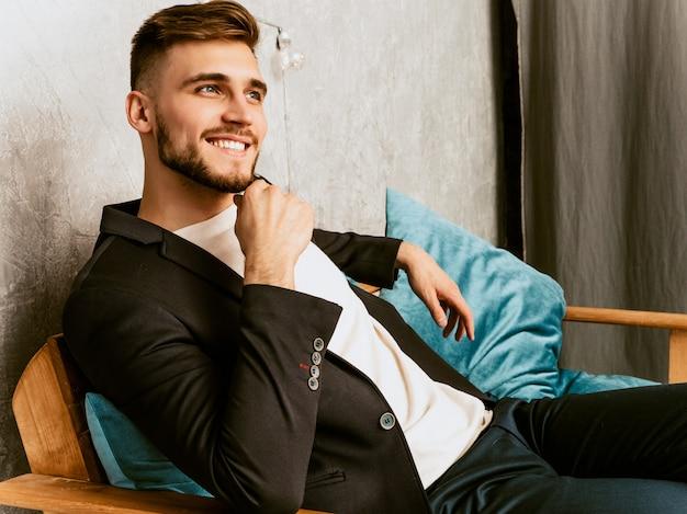 Ritratto del modello sorridente bello dell'uomo d'affari dei pantaloni a vita bassa che indossa vestito nero casuale.