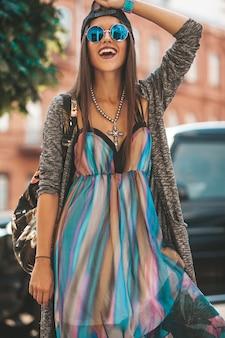 Ritratto del modello sorridente dell'adolescente castana di bello fascino in vestiti e borsa dei pantaloni a vita bassa di estate. ragazza in posa in strada. donna in occhiali da sole rotondi e cappello