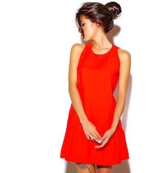 Ritratto del modello sveglio della giovane donna di modo in un vestito rosso su una parete bianca
