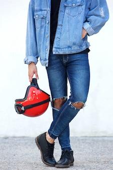 Ritratto del motociclista con i jeans strappati che tengono casco