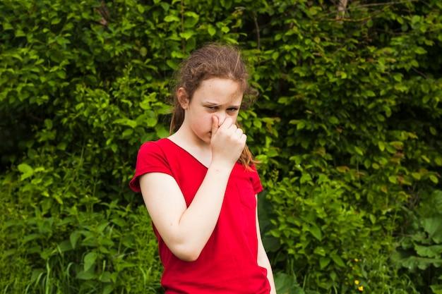 Ritratto del naso della tenuta della ragazza in natura verde che esamina macchina fotografica
