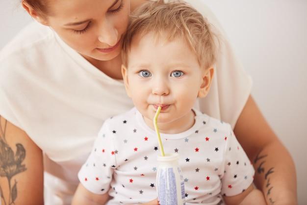 Ritratto del neonato biondo sveglio dagli occhi azzurri che beve attraverso la paglia