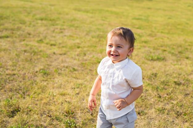 Ritratto del neonato felice sorridente su sfondo naturale di estate