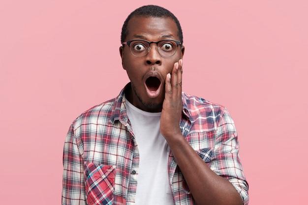 Ritratto del nerd studente maschio intelligente terrorizzato, indossa occhiali e camicia a scacchi, essendo scioccato per non superare l'esame e ricevere un brutto voto