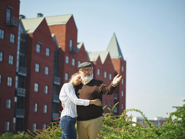 Ritratto del nonno d'abbraccio della ragazza al parco