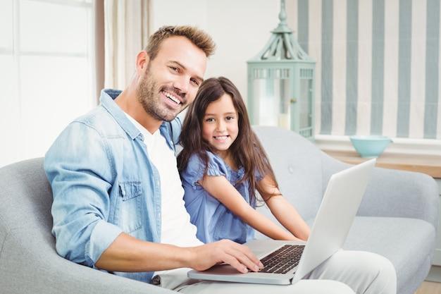 Ritratto del padre e della figlia felici che per mezzo del computer portatile