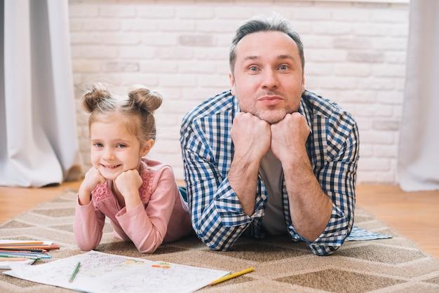 Ritratto del padre e della figlia sorridenti che si trovano sul tappeto che esamina macchina fotografica