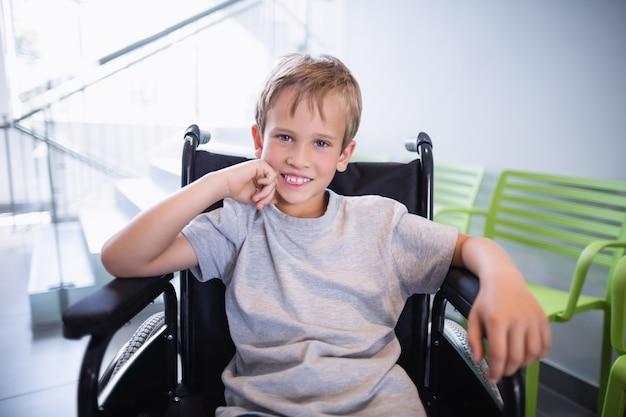 Ritratto del paziente sorridente del ragazzo che si siede su una sedia a rotelle