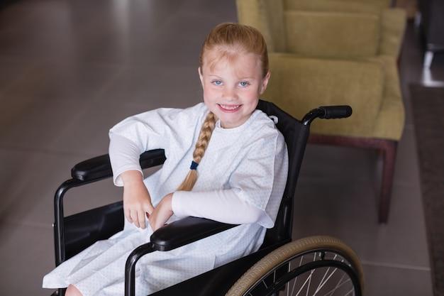Ritratto del paziente sorridente della ragazza che si siede su una sedia a rotelle
