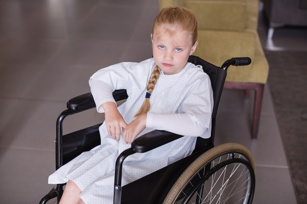 Ritratto del paziente triste della ragazza che si siede su una sedia a rotelle