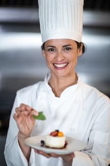 Ritratto del piatto femminile sorridente della tenuta del cuoco unico