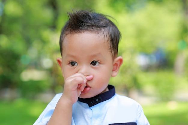 Ritratto del piccolo bambino asiatico che sente prurito sul suo naso nel giardino.