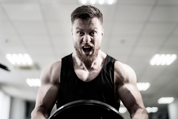 Ritratto del powerlifter muscolare bello con il disco del peso in sue mani nella palestra di sport. culturista con disco pesante allena i suoi bicipiti con la bocca aperta. avvicinamento. bianco e nero.
