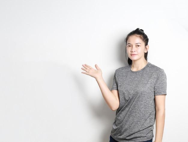 Ritratto del presentatore asiatico della donna su fondo bianco, donna asiatica che indica lo spazio della copia, bella ragazza tailandese.