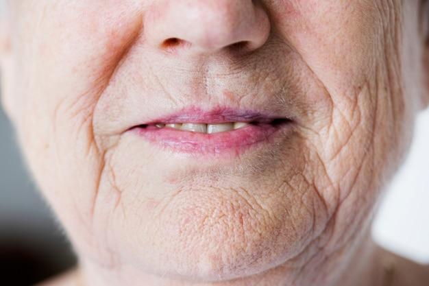 Ritratto del primo piano bianco della donna anziana sulle labbra sorridenti
